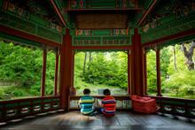 Rear View Of Boys Sitting In Gazebo At Park