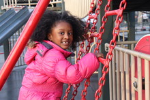 African American Girl On Playground Wearing Winter Coat
