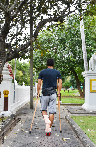 Fotografering Rear View Of Man With Fractured Leg Walking Using Crutches On Footpath
