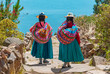 Leinwanddruck Bild - Two indigenous Quechua women in traditional clothes walking down the path to the harbor of Isla Taquile (Taquile Island) with the Titicaca Lake in the background, Peru.