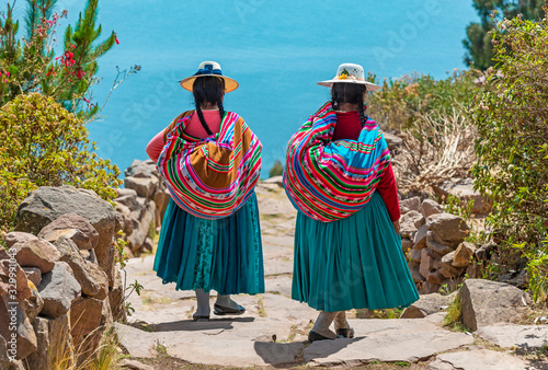 Obraz Two indigenous Quechua women in traditional clothes walking down the path to the harbor of Isla Taquile (Taquile Island) with the Titicaca Lake in the background, Peru. - fototapety do salonu