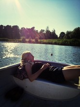 Young Woman Relaxing On Boat In Lake
