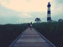 Rear View Of Woman Walking On Boardwalk Towards Lighthouse