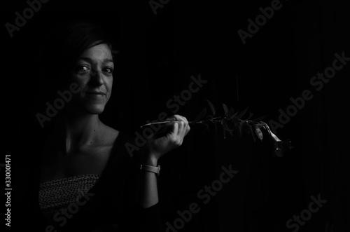 Fotografie, Obraz Portrait Of Smiling Holding Twig Against Black Background