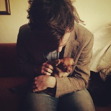 Young Man Petting Chihuahua Sitting In Lap