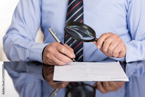 Fotografering Businessman examines the contract with the magnifying glass before signing it