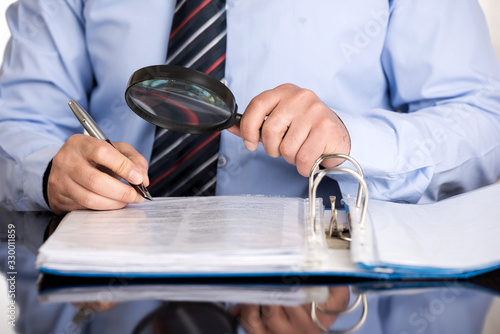 Businessman examines the file with the magnifying glass before signing it Tablou Canvas
