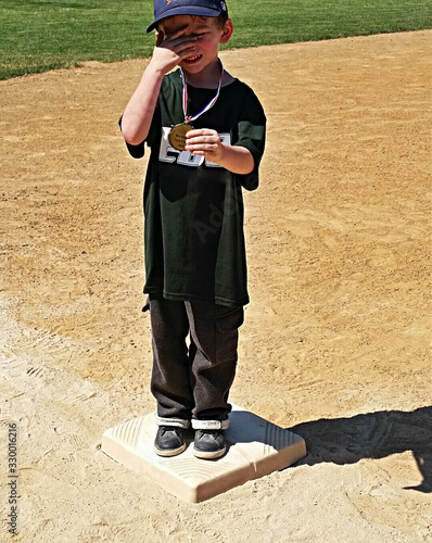 Canvas Print Boy Showing Medal While Standing On Baseball Base