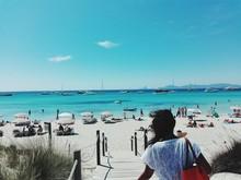 Rear View Of Woman Walking On Boardwalk On Illetas Beach Against Sky