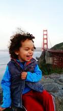 Cute Happy Boy Sitting On Rock By Golden Gate Bridge Against Clear Sky