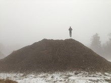 Man Levitating Above Heap Of Sand Against Clear Sky During Foggy Weather