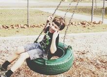 Happy Boy Riding On Tire Swing In Park