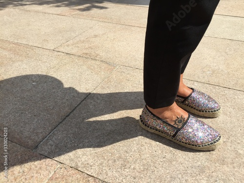 Obraz Low Section Of Woman Standing On Footpath With Glittering Shoes And Shadow - fototapety do salonu