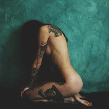 Full Length Of Naked Tattooed Woman Kneeling Against Green Wall