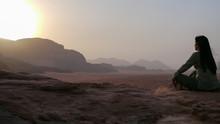 Woman Meditating At Desert Against Sky During Sunrise