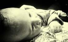 Close-up Of Cute Baby Resting On Mother Abdomen At Home