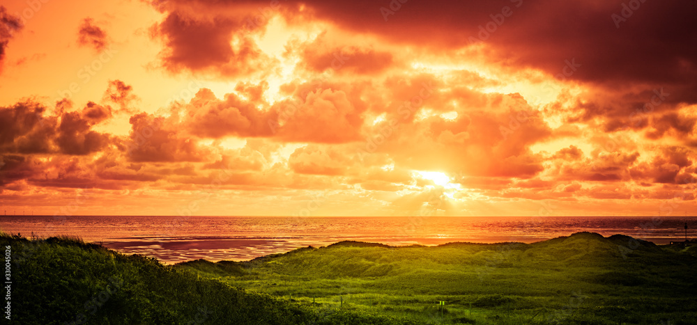 Fototapeta Sonnenuntergang über dem Meer in einer Dünenlandschaft