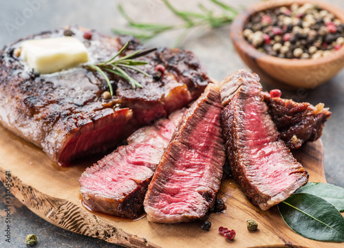 Fototapeta Medium rare Ribeye steak with herbs and a piece of butter on the wooden tray. obraz