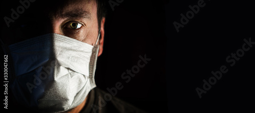 Obraz portrait of a man in a medical mask in a low key. a worldwide tragedy. COVID-19 virus pandemic warning - fototapety do salonu