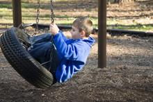 Boy Enjoying Tire Swing On Playground