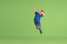 Dabbing. Happy Boy Playing And Having Fun On Green Studio Background. Caucasian Kid In Bright Cloth Looks Playful, Laughting, Smiling. Concept Of Education, Childhood, Emotions, Facial Expression.