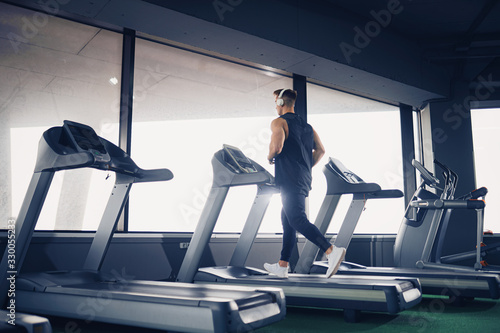 fototapeta na lodówkę Profile view of concentrated fit man listening to music in headphones while running on treadmill in modern gym with panoramic windows, portrait shot.