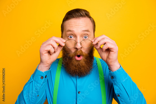 Obraz Closeup photo of attractive red head guy taking off specs excited good eyesight after correction operation wear bright blue shirt green suspenders isolated yellow color background - fototapety do salonu