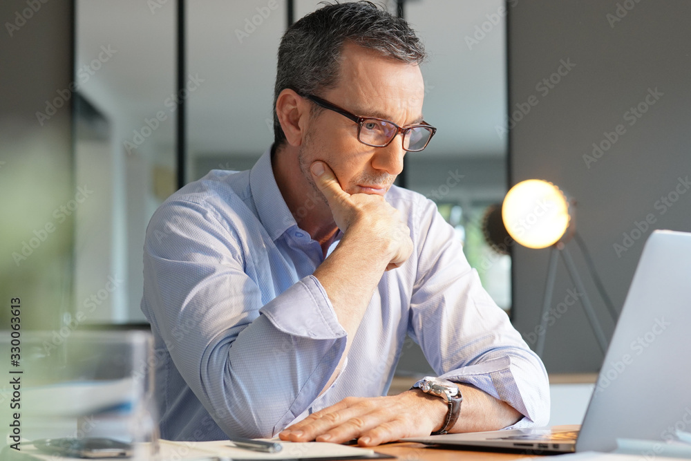 Fototapeta Business manager working in office on laptop