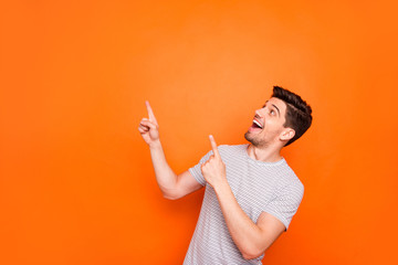 Photo of attractive funny crazy guy hold hands fingers direct up empty space excited good mood sales person wear striped t-shirt isolated bright orange color background