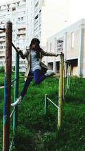 Woman Climbing On Jungle Gym At Playground