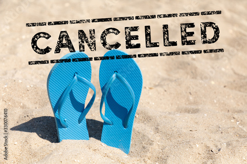 Fotografía flip flops in the sand and text cancelled - vacation cancel