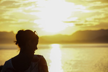 Silhouette Of Woman Looking Away While Standing By Sea At Sunset