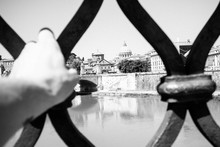 Cropped Hand Of Person On Metal Grate Against St Peter Basilica Seen From Ponte Santangelo