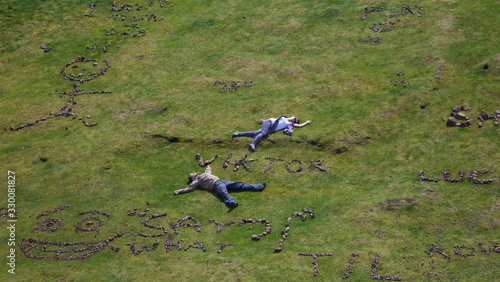 Photo High Angle View Of Man And Woman Lying By Text Made With Stone At Arthur Seat