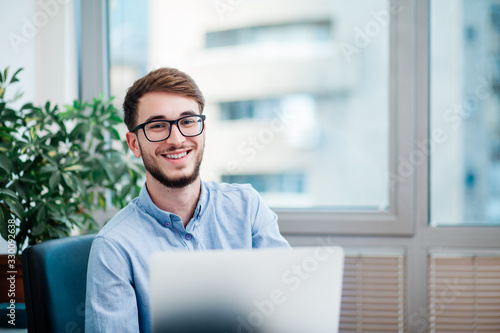 Canvas Print Young businessman in office working on laptop