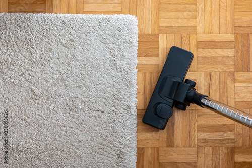 Vacuum cleaner extension on a laminated wooden floor next to a grey fabric rug Slika na platnu