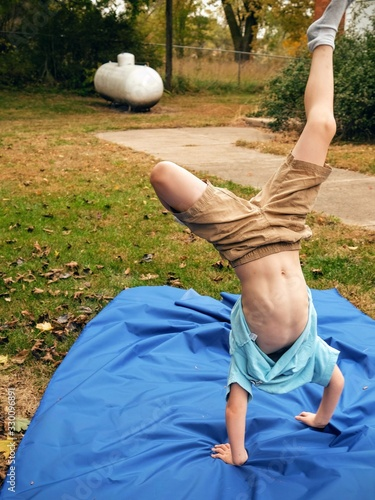 Tablou Canvas Full Length Of Boy Performing Handstand On Blue Fabric In Yard