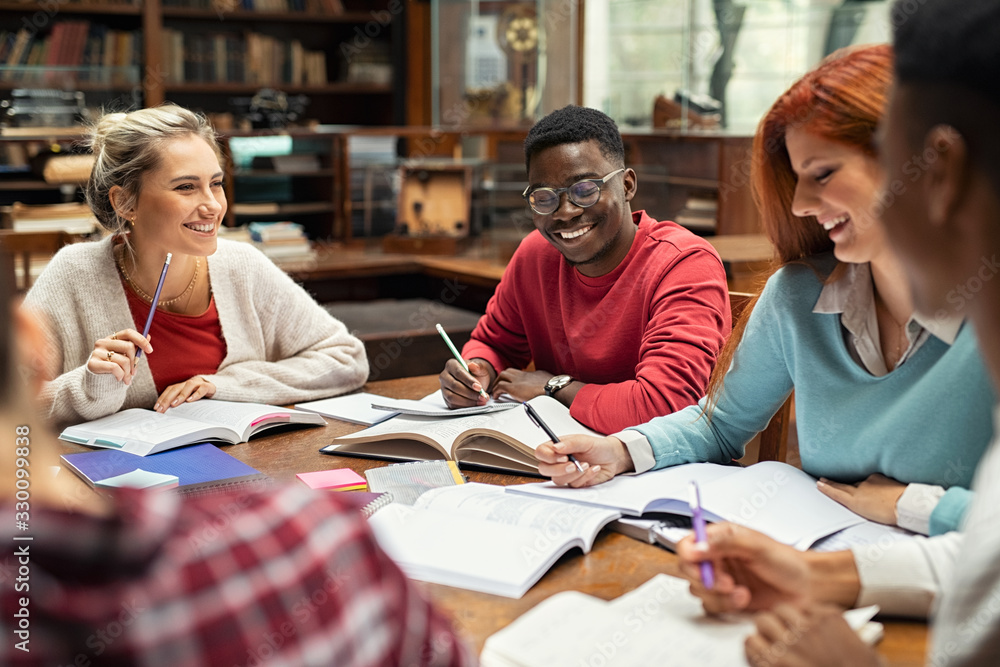 Fototapeta Happy college students studying together