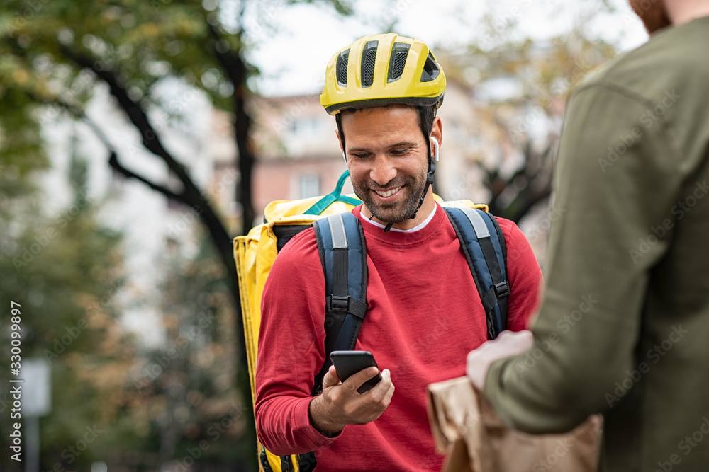 Fototapeta Delivery man checking food order with smartphone