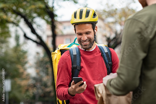 Obraz Delivery man checking food order with smartphone - fototapety do salonu