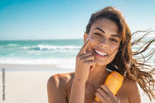 Obraz Smiling woman applying sunscreen - fototapety do salonu