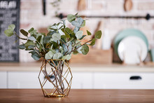 Metallic Geometric Decorative Through Vase With Artificial Eucalyptus Branches On A Wooden Table.