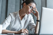 Stressed young female office worker sitting at desk holding head because of pain in office