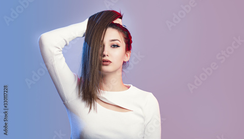 Photo portrait of cocky girl with long ponytail hair on studio background, young woman