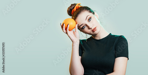 portrait of a beautiful young woman with bun hairstyle holding orange near head, Canvas Print