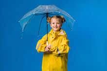 Child Girl Blonde Smiling In A Yellow Raincoat And Rubber Boots Holding An Umbrella Stands On A Blue Background In The Studio, Space For Text