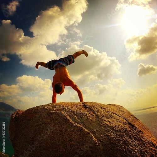 Fototapeta Shirtless Man Doing Handstand On Rock Against Sky During Sunset