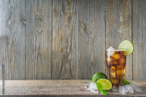 Obraz Summer iced alcohol drink with cola and lime. Rum and cola Cuba Libre cocktail. One long glass on wooden background copy space - fototapety do salonu