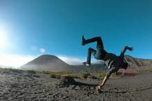 Person Doing Acrobatic Stunt In Landscape