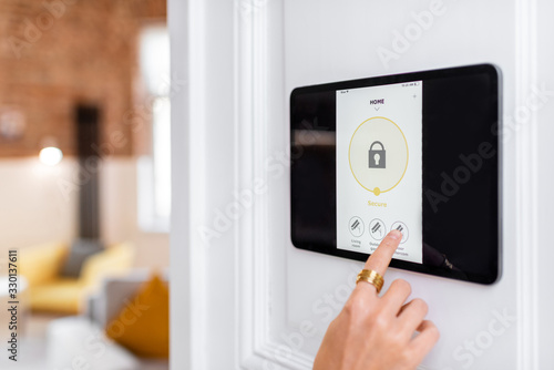 Controlling home alarm system with a digital touch screen panel installed on the wall Canvas Print